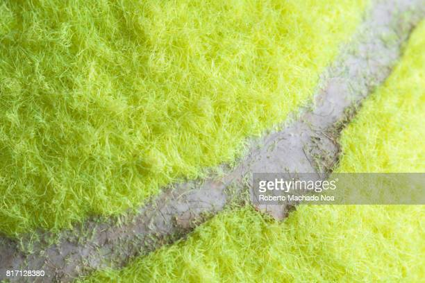 Industrial imperfections: tennis ball close up. The object is fluorescent yellow covered in a fibrous felt