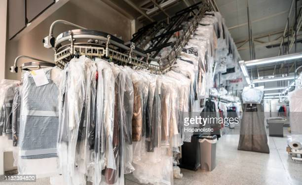 industrial laundry service with conveyor belt - dry cleaner stock pictures, royalty-free photos & images