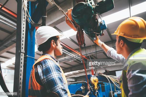 industrial machinery male employees working with remote control for operating crane - crane stock pictures, royalty-free photos & images