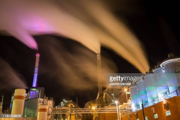 industrial plant with chimney smoke at night - 工場地帯 ストックフォトと画像