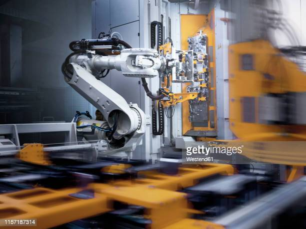 industrial robot in modern factory - industriebetrieb stock-fotos und bilder