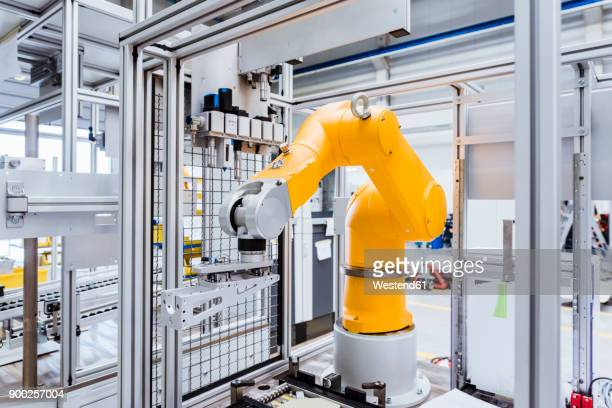 industrial robot on factory shop floor - automation stock pictures, royalty-free photos & images