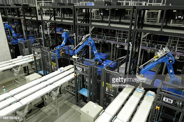 Industrial robots manufactured by Yaskawa Electric Corp place boxes of pharmaceutical products onto conveyor belts at a Toho Pharmaceutical Co...