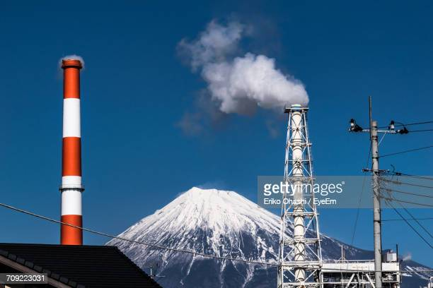 Industrial Smokestack Against View Of Mount Fuji