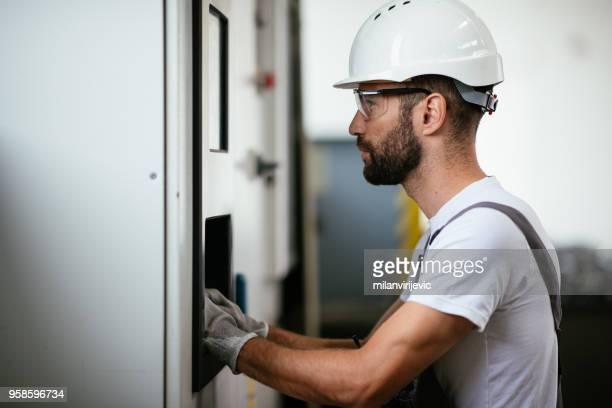 Industriële technicus die in elektriciteit onderstation