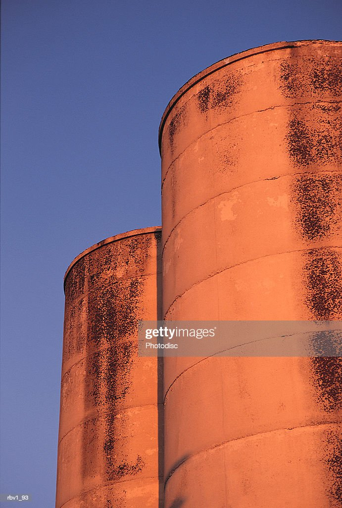 industrial towers seem orange under a blue sky as the sun sets : Foto de stock