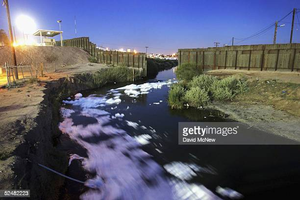 Industrial waste suds are carried by the New River, reportedly the most polluted river in the US, as it flows through the US/Mexico border fence from...