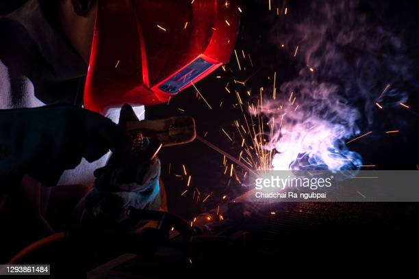 industrial welder worker working construction welding with welding mask in factory on the machine. - fabricage apparatuur stock pictures, royalty-free photos & images