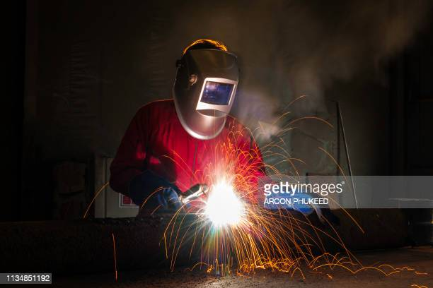 industrial welder working a welding metal with protective mask and sparks on piping work - fabricage apparatuur stock pictures, royalty-free photos & images