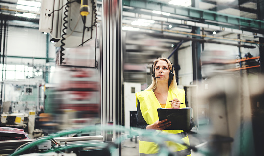 Industrial woman engineer with headset in a factory, working. Copy space. 1087179354