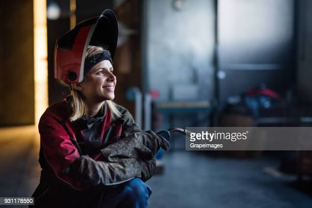industrial woman worker at the welding factory. - welding stock photos and pictures