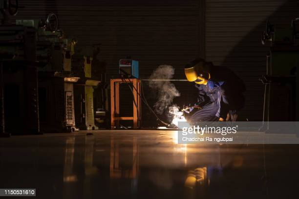 industrial worker at the factory welding closeup - fabricage apparatuur stock pictures, royalty-free photos & images