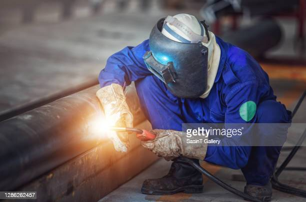 industrial worker at the factory welding - fabricage apparatuur stock pictures, royalty-free photos & images