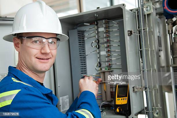 Industrial worker in a hard hat working on a circuit box