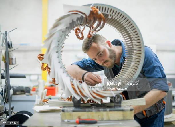 industrial worker in blue overall in electric motor factory - electric motor stock photos and pictures