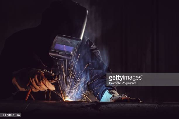 industrial worker labourer at the factory welding steel structure. - fabricage apparatuur stock pictures, royalty-free photos & images