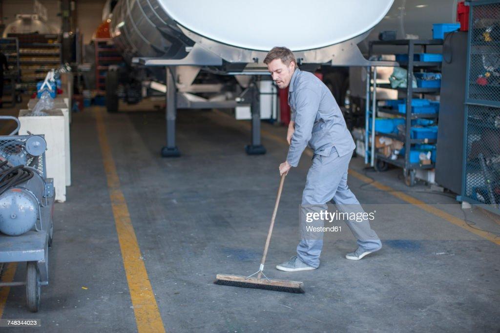 Industrial worker sweeping floor : Stock Photo