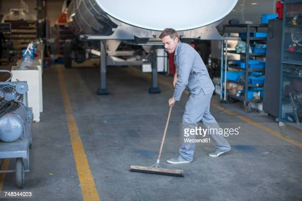 Industrial worker sweeping floor