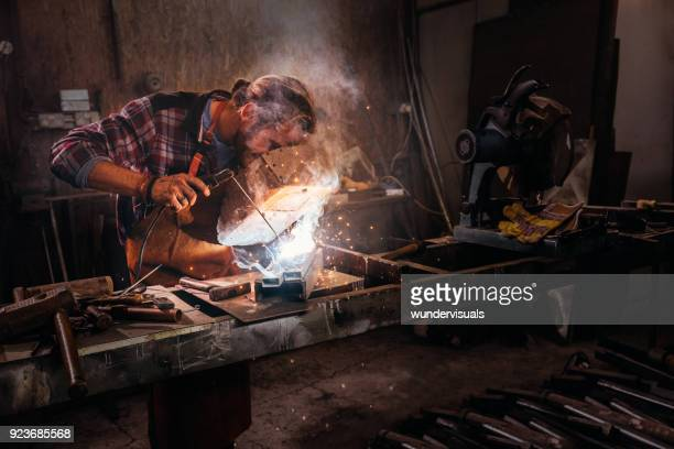 industrial worker welding metal using protective mask in workshop - in flames i the mask stock pictures, royalty-free photos & images