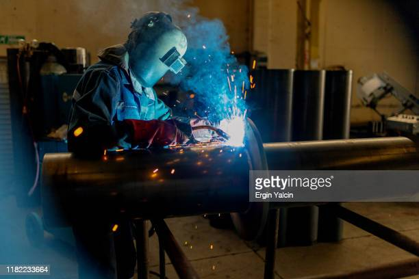 industrial worker welding on the pipe - in flames i the mask stock pictures, royalty-free photos & images
