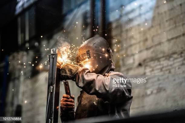 industrial worker welding steel - in flames i the mask stock pictures, royalty-free photos & images