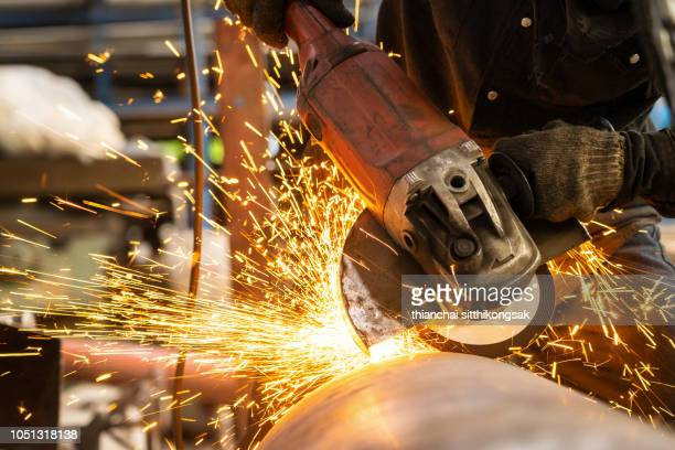 Industrial worker with heavy tool in machinery shop