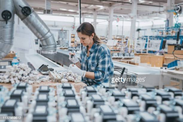 industrial worker woman soldering cables of manufacturing equipment in a factory - electronics industry stock pictures, royalty-free photos & images