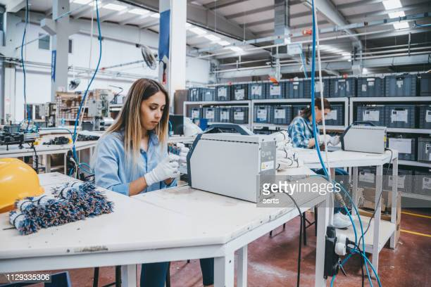 industrial worker woman working together with manufacturing equipment in a factory - mechatronics stock pictures, royalty-free photos & images
