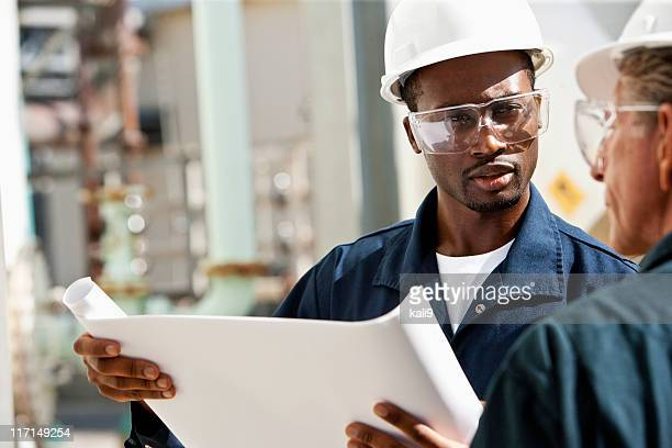industrial workers reviewing plans - storage tank stock photos and pictures
