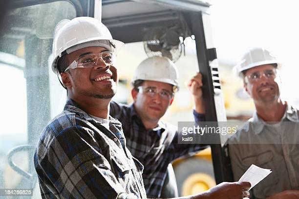 Trabalhadores industriais com máquina elevadora de cargas