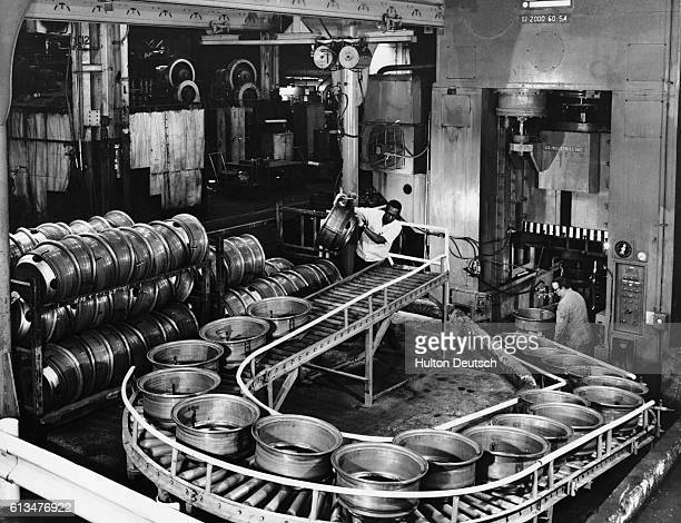 Industrial workers work on a production line transporting wheels to the processing operation at the US Budd Company subsidiary plant
