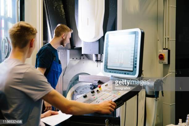 industrie 4.0: zwei junge ingenieure steuern die arbeit an einer cnc-maschine - rechnerunterstütztes konstruieren stock-fotos und bilder