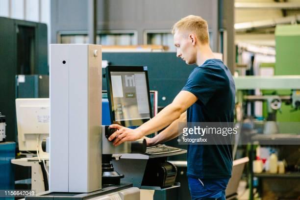 industrie 4.0: junger ingenieur steuert seine arbeit an einer cnc-maschine - rechnerunterstütztes konstruieren stock-fotos und bilder