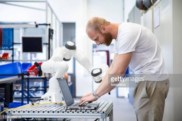 industrie 4.0: junger ingenieur arbeitet an einem roboterarm - rechnerunterstützte fertigung stock-fotos und bilder