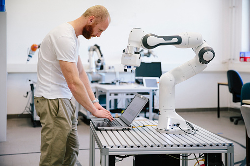 industry 4.0: Young engineer works at a robotic arm 1156496520