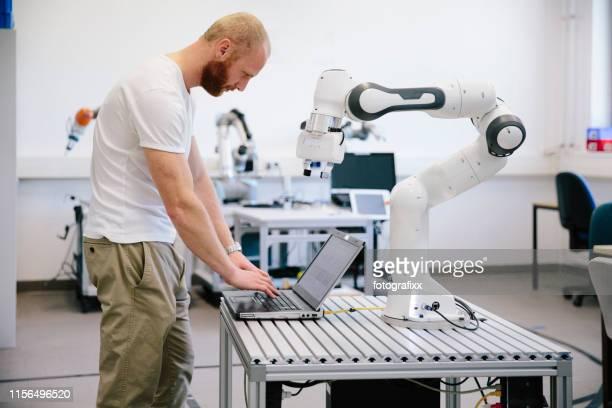 industrie 4.0: junger ingenieur arbeitet an einem roboterarm - automatisiert stock-fotos und bilder