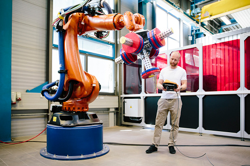 industry 4.0: Young engineer works at a robotic arm 1157298016