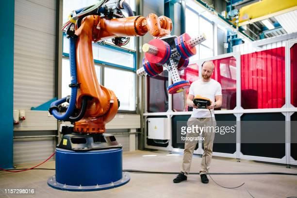 industry 4.0: young engineer works at a robotic arm - robot stock pictures, royalty-free photos & images
