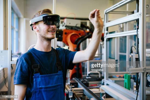 industrie 4.0: junger ingenieur arbeitet mit einem kopfdisplay - virtual reality simulator stock-fotos und bilder