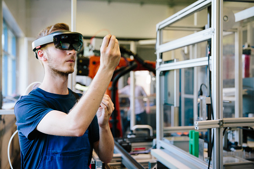 industry 4.0: Young engineer works with a head-mounted display 1156535018