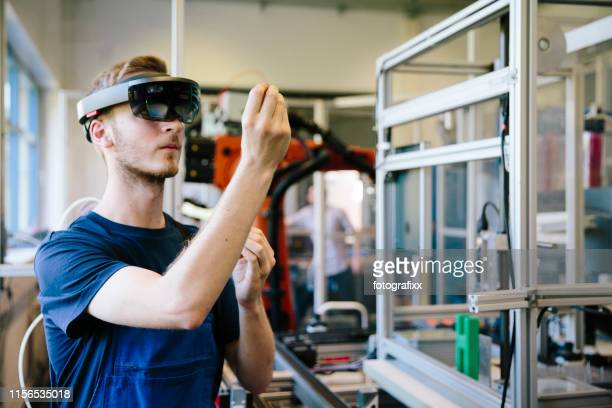 industry 4.0: young engineer works with a head-mounted display - simulatore di realtà virtuale foto e immagini stock
