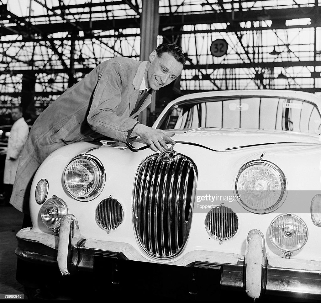 Industry. England 1957. Jaguar Motor Car Factory. A production line worker inspects the badge on the radiator grill of a car. : News Photo
