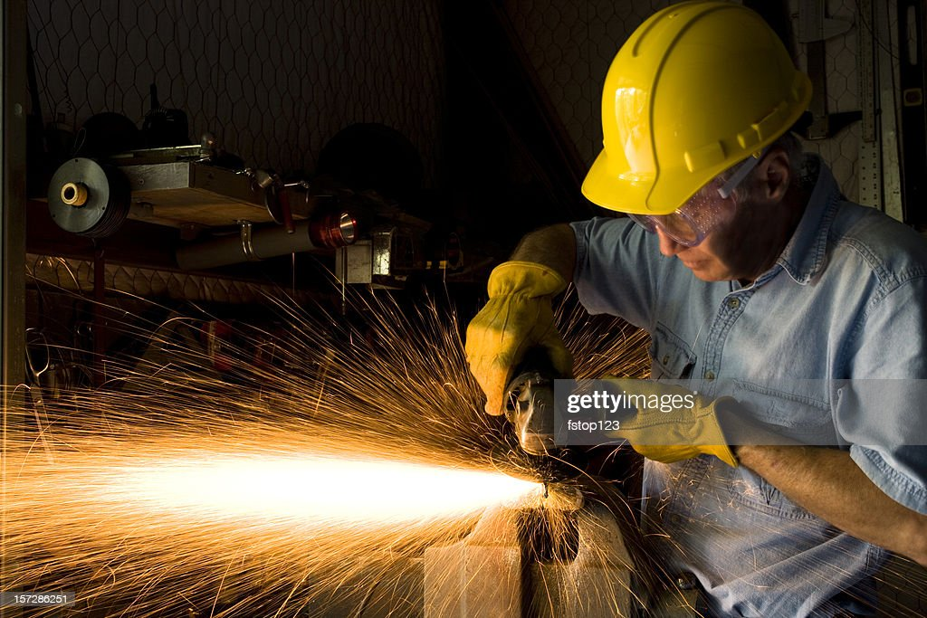 Industry: Man Grinding in workshop wearing hardhat and gloves.  Sparks : Bildbanksbilder