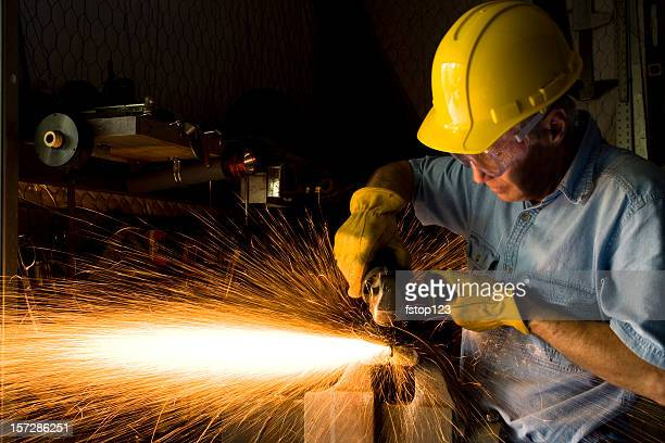 Industry: Man Grinding in workshop wearing hardhat and gloves.  Sparks