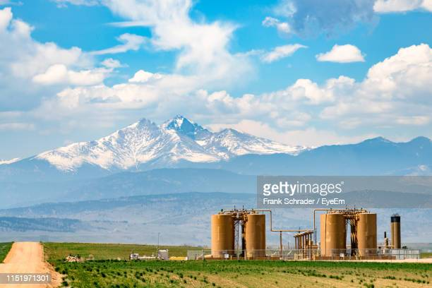industry on field by mountains against sky - frank schrader stock pictures, royalty-free photos & images