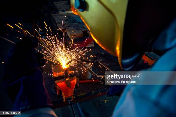 industry worker welder working welding steel metal safety mask safety gloves and safety equipment - male erection stock pictures, royalty-free photos & images