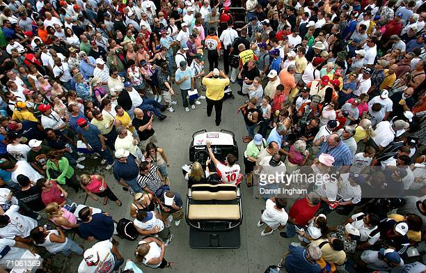 Indy 500 winner Dan Wheldon driver of the Target Ganassi Racing Dallara Honda waves to the crowd as he passes through Gasoline Alley during...