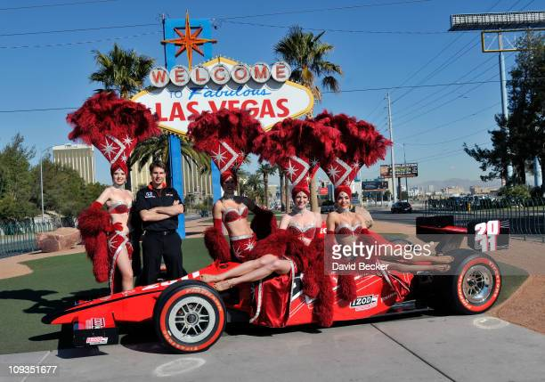 Indy Car driver Will Power of Australia driver of the Verizon Team Penske poses with Las Vegas showgirls at the 'Welcome to Fabulous Las Vegas' sign...
