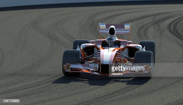Indy race car on a track covered in tire marks