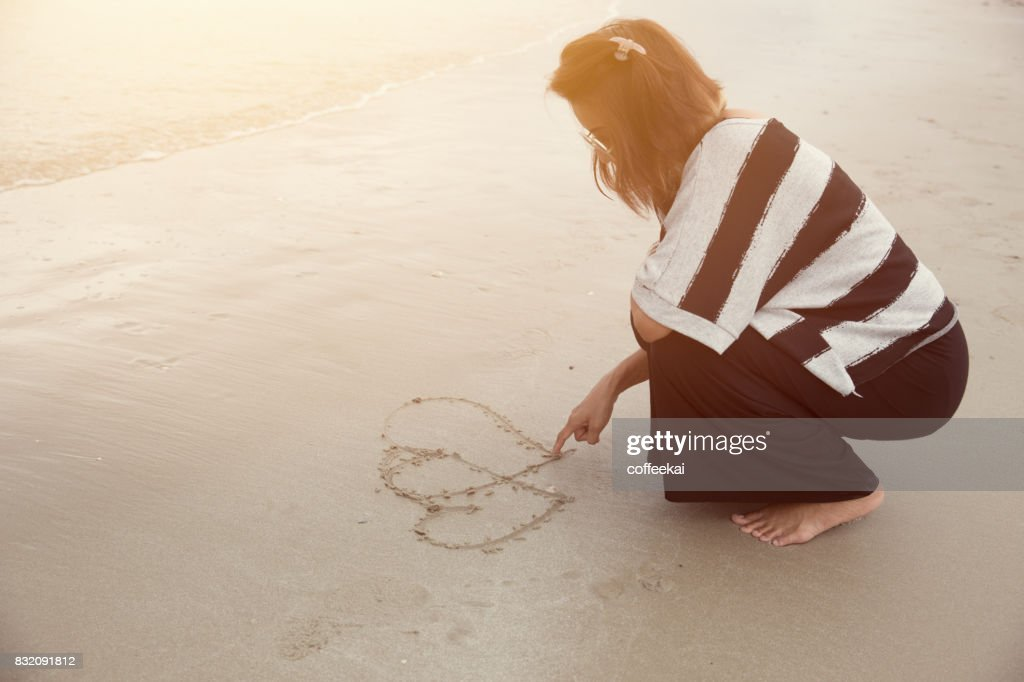Indy Women Alone Draw Heart Shape On The Beach Vintage Color Tone